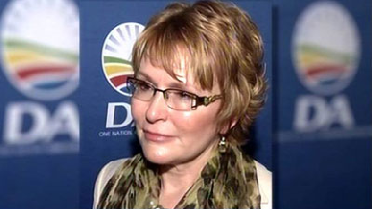 Helen Zille standing in front of a DA logo