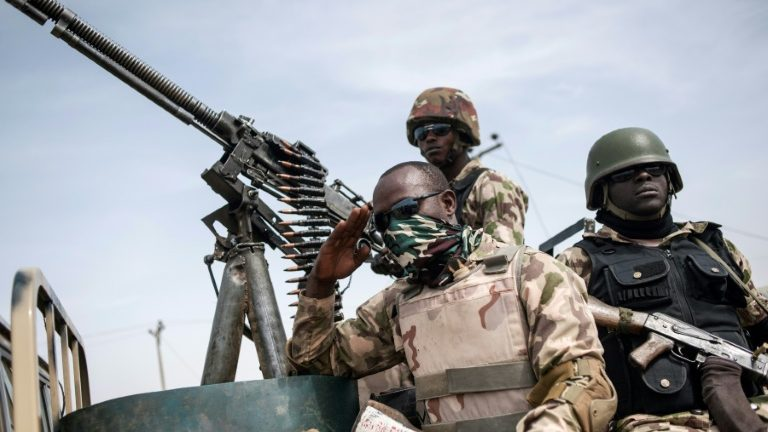Three men in a car next to a machine gun