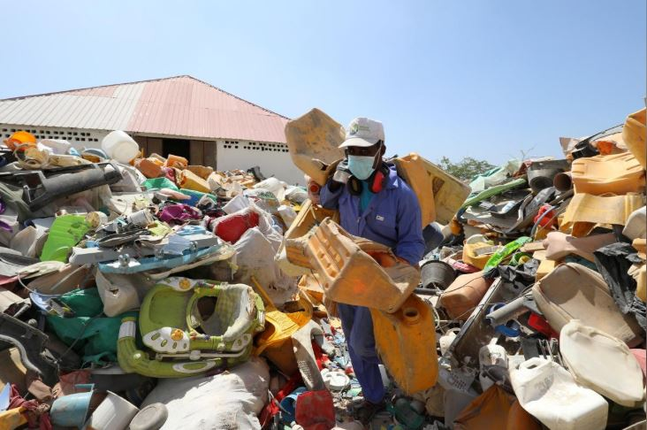 A man sorts plastic litter collected from a garbage dump to be recycled into roofing tiles at the Envirogreen recycling plant.