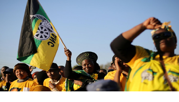 ANC members standing with flag.