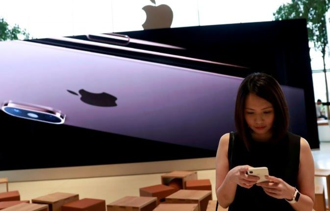 A woman checks her phone at a flagship Apple store at Iconsiam shopping mall in Bangkok.