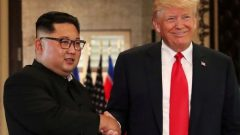 U.S. President Donald Trump and North Korea's leader Kim Jong Un shake hands after signing documents during a summit.
