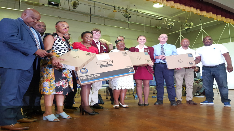 Deputy Minister Pinky Kekana with members of the Louis Trichardt high school holding laptops