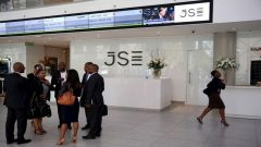 File: People chat in front of a reception with an electronic board displaying movements in major indices at the Johannesburg Stock Exchange building in Sandton Johannesburg, March 14, 2016.
