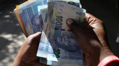 FILE PHOTO: A street money changer counts South African Rands in Harare