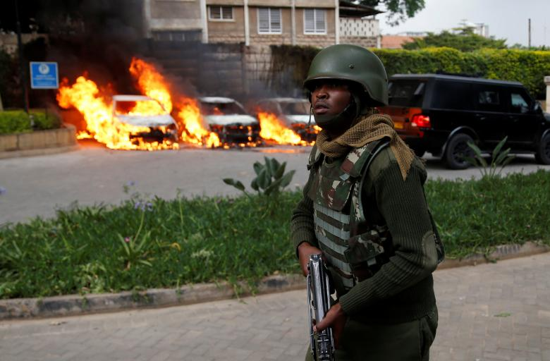 A member of security forces walks as cars are seen on fire at the scene where explosions and gunshots were heard at the Dusit hotel compound, in Nairobi.
