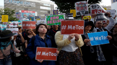Protesters holding placards against sexual harassment