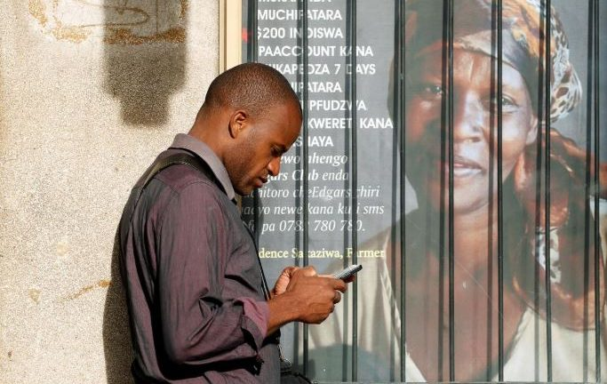 A man checks his mobile phone, in Harare, Zimbabwe.