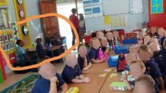 Black learners sitting at a corner table and white learners sitting on one table