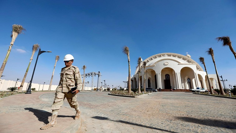 A member of Egyptian Army walks outside the new Coptic Cathedral