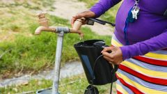 A resident fills a plastic kettle with water from a communal tap