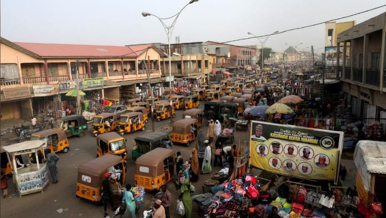 Taxis called in a local language Keke-Napep move in a street after the postponement of the presidential election in Kano, Nigeria.