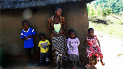 Five children standing outside a hut