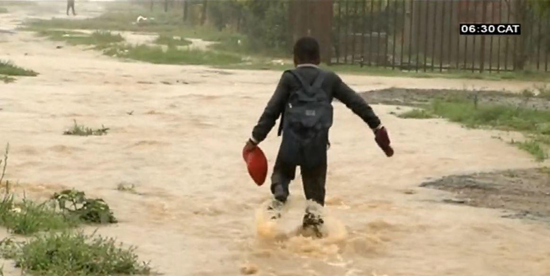 Boy walking through flooded path