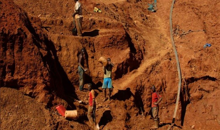 Illegal artisanal gold miners work at an open mine