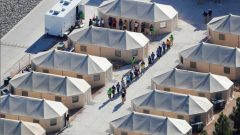 "Immigrant children now housed in a tent encampment under the new ""zero tolerance"" policy by the Trump administration are shown walking in single file at the facility near the Mexican border."