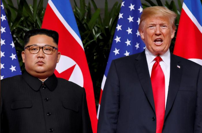 US President Donald Trump and North Korean leader Kim Jong Un react at the Capella Hotel on Sentosa island in Singapore.