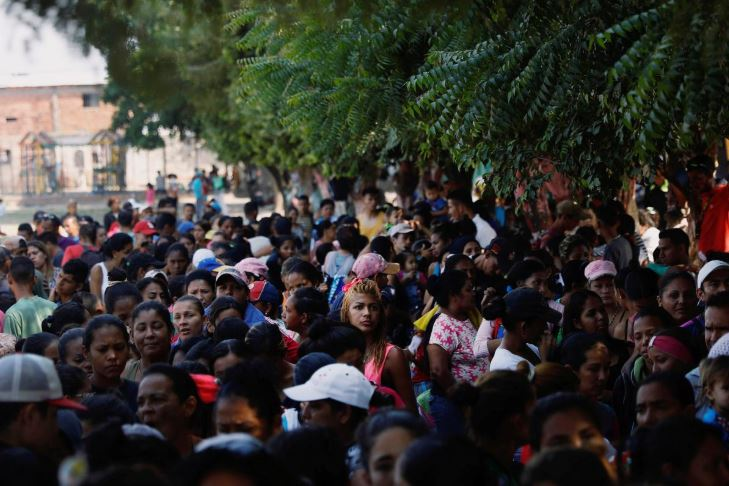 """Venezuelans line up as they wait for a free lunch at the """"Divina Providencia"""" migrant shelter outskirts of Cucuta."""
