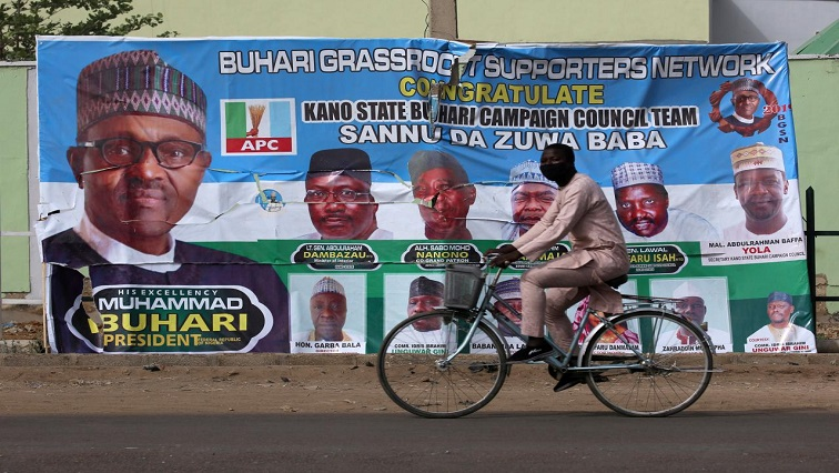 A cyclist drives pasts a campaign poster for President Muhammadu Buhari.