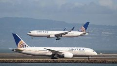 A United Airlines Boeing 787 taxis as a United Airlines Boeing 767 lands at San Francisco International Airport.