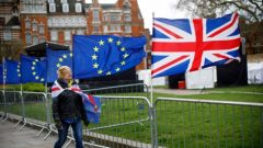 Woman walks past EU and UK flags