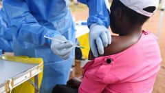 A Congolese health worker administers Ebola vaccine to a boy who had contact with an Ebola