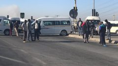 Taxi drivers stand on a road.