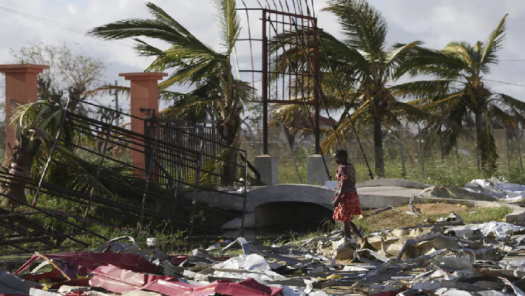 A woman searches for materials to rebuild her home after the passage of Cyclone Idai, in Beira City, central Mozambique.