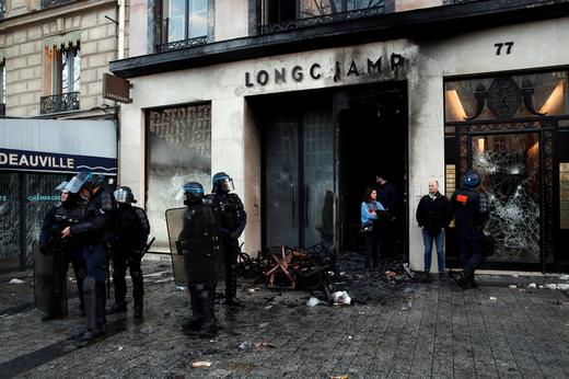 "The damaged window of a Longchamp shop is pictured on the Champs-Elysees after a demonstration by the ""yellow vests"""