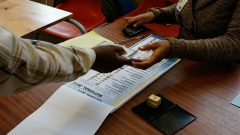 A voter receives ballot papers from election official in Johannesburg in 2014.