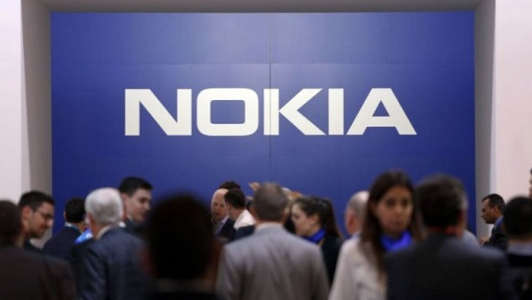 People standing in front of Nokia logo