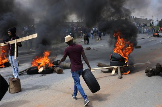 A man walks with a car tyre as he barricades the street during a service delivery protest in Alexandra township.