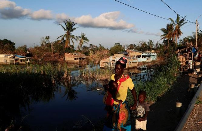 A woman walks with her children past flooded houses in the aftermath of Cyclone Idai in Tica near Beira.