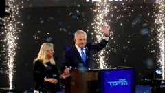 Confetti falls as Israeli Prime Minister Benjamin Netanyahu and his wife Sara stand on stage after Netanyahu spoke following the announcement of exit polls in Israel's parliamentary election at the party headquarters in Tel Aviv.