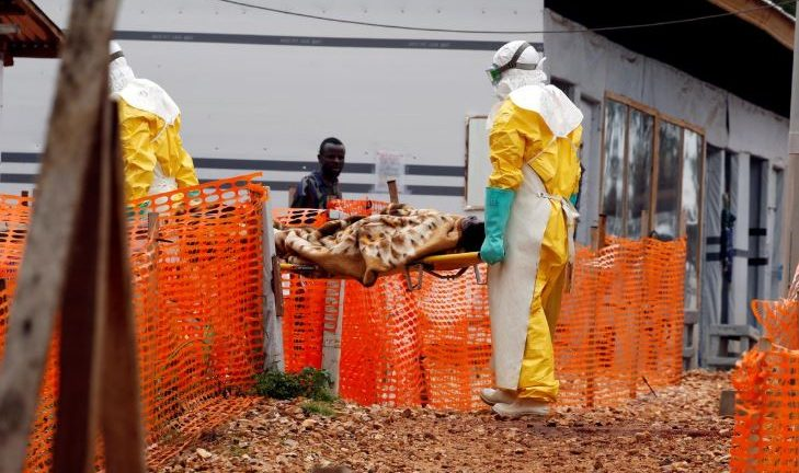 Health workers carry a newly admitted confirmed Ebola patient