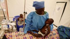 Ebola survivor Jeanine Masika holding two-year-old ebola patient, Furana Katungu