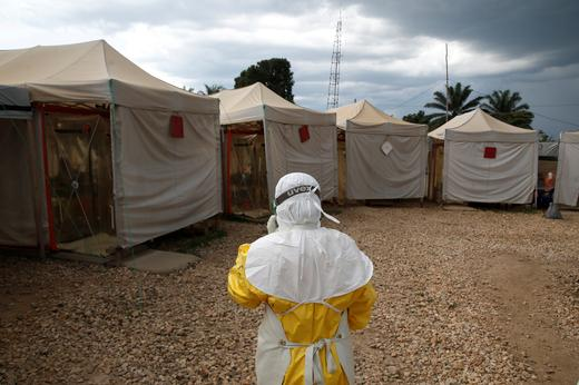 A health worker wearing Ebola protection gear, walks before entering the Biosecure Emergency Care Unit (CUBE).