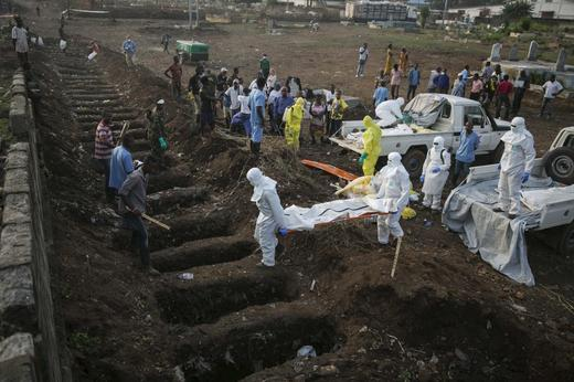 Health workers carry the body of an Ebola victim for burial at a cemetery in Freetown.