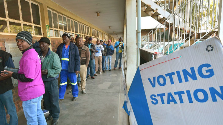 People standing in a line outside voting station