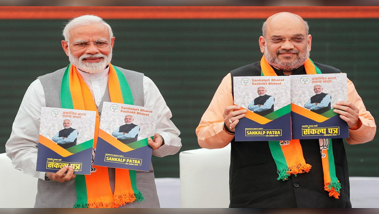 Prime Minister Narendra Modi and chief of the Bharatiya Janata Party (BJP) Amit Shah, display copies of their party's election manifesto