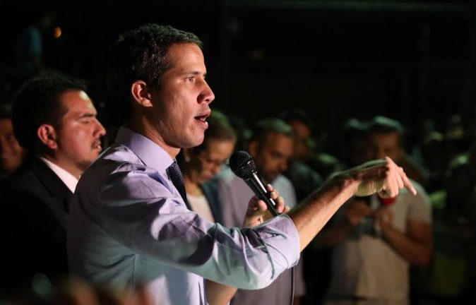 Venezuelan opposition leader Juan Guaido, who many nations have recognized as the country's rightful interim ruler, talks to the media during a news conference in Caracas.