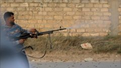 A member of the Libyan internationally recognised government forces fires during fighting with Eastern forces in Ain Zara.