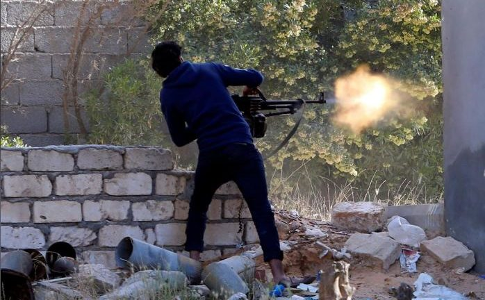 A member of the Libyan internationally recognised government forces fires during a fight with Eastern forces in Ain Zara, Tripoli, Libya.