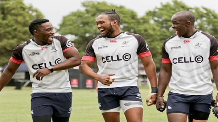 Three rugby players laughing