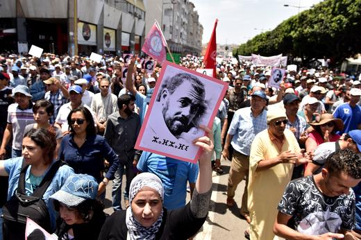 Protesters hold a portrait of protest movement leader Nasser Zefzafi and shouts slogans during a demonstration against corruption.