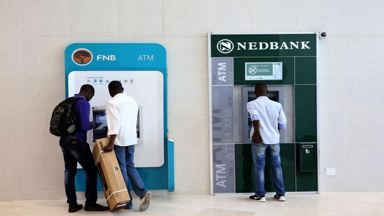 People standing by FNB and Nedbank ATMs