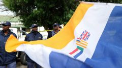 The apartheid flags displayed in public with SAPS officers in the background