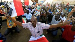 Sudanese demonstrators hold their national flag and chant slogans as they attend a mass anti-government protest outside Defence Ministry in Khartoum
