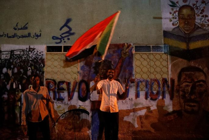 A Sudanese protester waves a national flag as he arrives a mass protest in front of the Defence Ministry in Khartoum, Sudan.