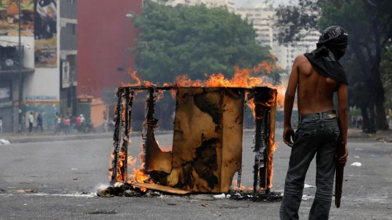 A demonstrator stands next to a burning barricade during a protest against the government of Venezuelan President Nicolas Maduro in Caracas.